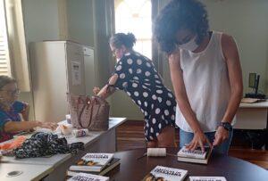Servidoras preparam os kits de livros para doação.
